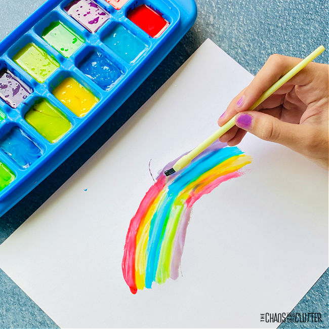 a blue ice cube tray is filled with paint colours and a rainbow is being painted on a white paper
