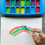 ice cube tray with paint while a hand paints a rainbow with a yellow brush