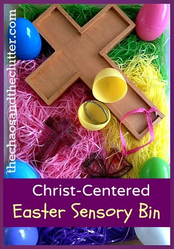 Christ-Centered Easter Sensory Bin with plastic eggs, paper grass, and a wooden cross.