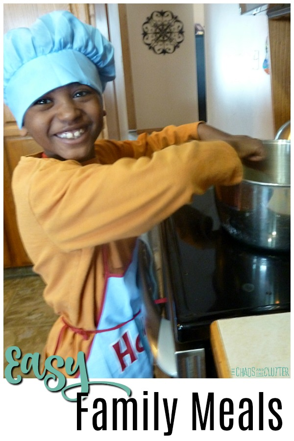 "a cute black boy wearing an orange shirt, blue and red apron, and blue chef hat smiles as he stirs in a pot on the stove. The text reads ""Easy Family Meals"""