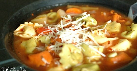 close up of tortellini soup garnished with cheese