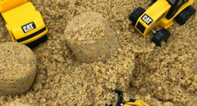 a white bin filled with kinetic sand also contains 3 small construction vehicle toys that are yellow and black in colour.