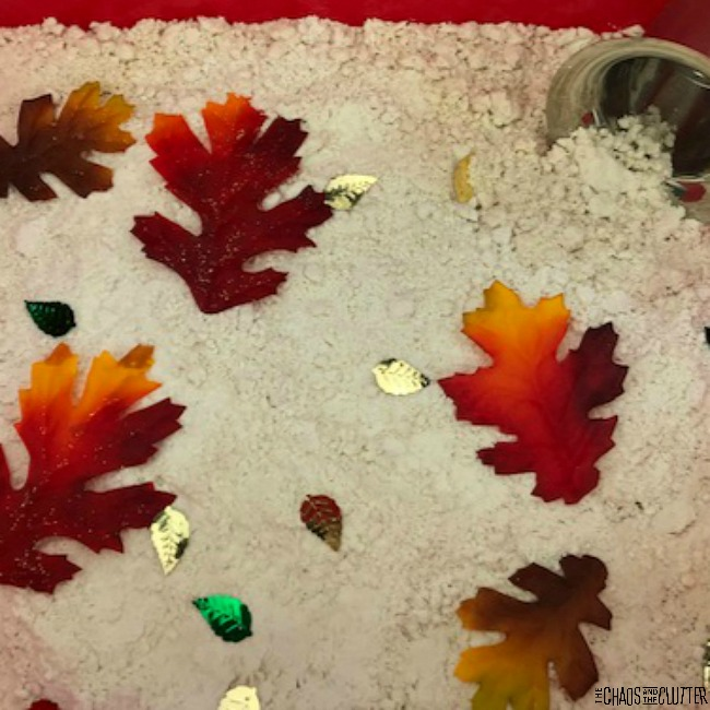 in a red plastic bin, light almost white cloud dough is sprinkled with fall coloured plastic leaves and small metallic leaf shaped confetti. There is also a metal scoop in the corner.