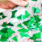 an almost opaque white slime with red round confetti and bright green tree shaped confetti is seen held in a hand with only the thumb visible