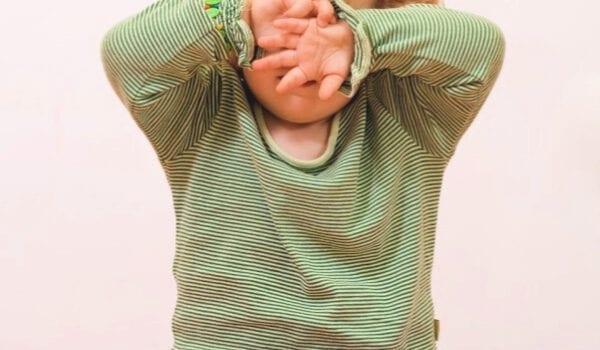 "a young girl wearing a green and white striped long sleeve shirt and pink pants sits cross legged on the floor with her hands covering her eyes. The words ""How to Stop Sensory Overload from Turning into a Sensory Overload""."