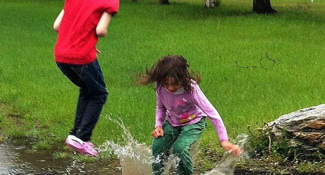 There are trees in the background and bright green grass. Two young girls, one wearing a red t-shirt and black pants with pink shoes, the other wearing a pink long sleeved shirt and green pants are splashing in a puddle. The water splash comes up higher than the girl in the green pants' knees. The other girl is jumping in the air.