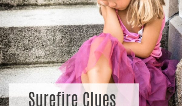 """A little girl in a pink princess dress with blonde pigtails and a gold decoration in her hair sits with one leg crossed over the other on a grey outdoor staircase. The words """"Surefire Clues Your Child has Sensory Issues"""" are overlaid on the image."""