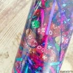 A closeup picture of a sensory bottle filled with bright colours of alphabet beads and bright coloured tinsel.