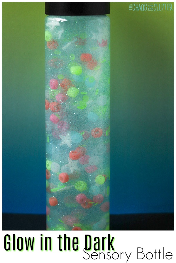 bottle filled with multicoloured beads and stars and liquid on a blue and green background