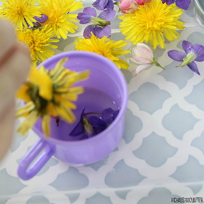 a child's hand dipping a yellow dandelion into water in a purple cup that is inside a sensory bin filled with water and other flowers