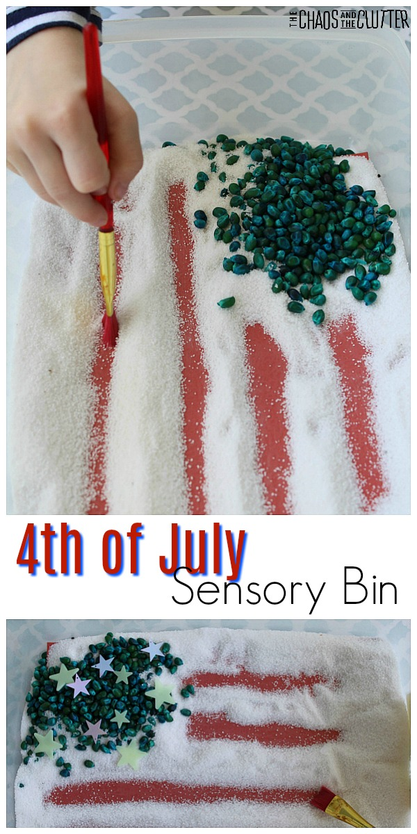 "In the top part of the image, a young child's hand holds a red paintbrush and is brushing aside white sand to reveal red paper underneath. There is a pile of blue popcorn kernels in the corner. The words ""4th of July Sensory Bin"" are in the middle of the image. On the bottom is a sensory bin with red stripes in white sand, a pile of blue popcorn in the top corner, and stars sprinkled on top of the popcorn kernels."