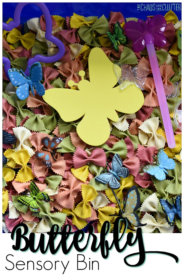 "Brightly coloured bow tie shaped dry pasta is in a blue plastic bin. Resting on the pasta are blue and green plastic butterflies, a large yellow butterfly shaped foam piece, a pink butterfly wand, and a purple butterfly shaped cookie cutter. The words ""Butterfly Sensory Bin"" are on the bottom of the image."
