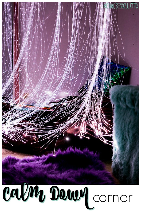 Strings of white fibre optic lights hang over a brown bean bag chair with a mermaid pillow. There is a purple throw carpet in the foreground.