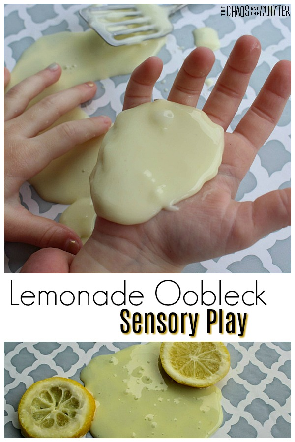 "A young child's hands are visible. With one hand, he is touching a light yellow slimey substance that is on a table and with the other hand, he is holding the yellow substance in the palm of his open hand. The words ""Lemonade Oobleck Sensory Play"" appear on white in the middle of the image and at the bottom, the light yellow substance is spread on a table and there are two lemon slices on top of it."