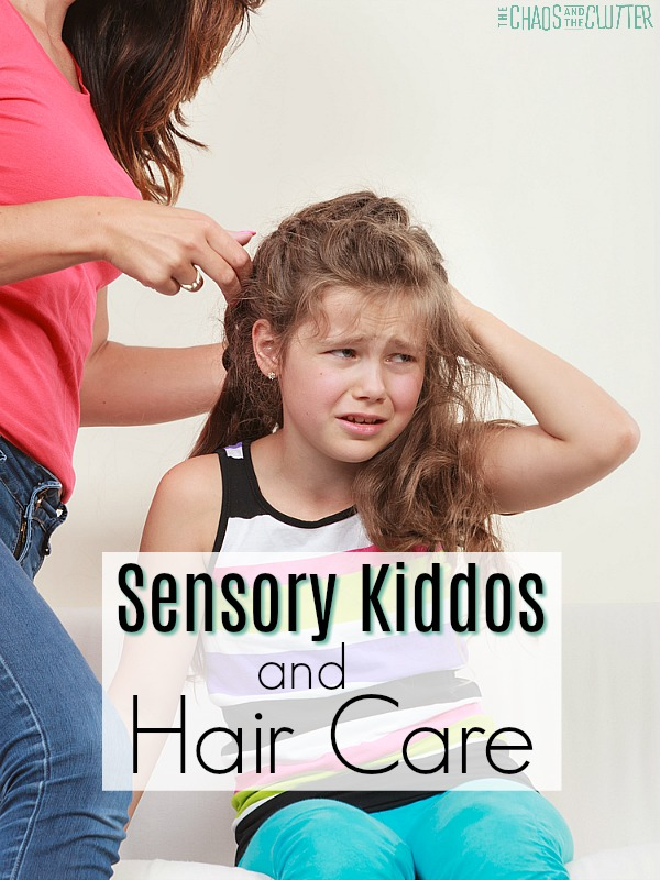 "a woman in a coral shirt and jeans tries to comb her daughter's hair. The daughter looks very distraught. The words ""Sensory Kiddos and Hair Care"" are overlaid on the image."