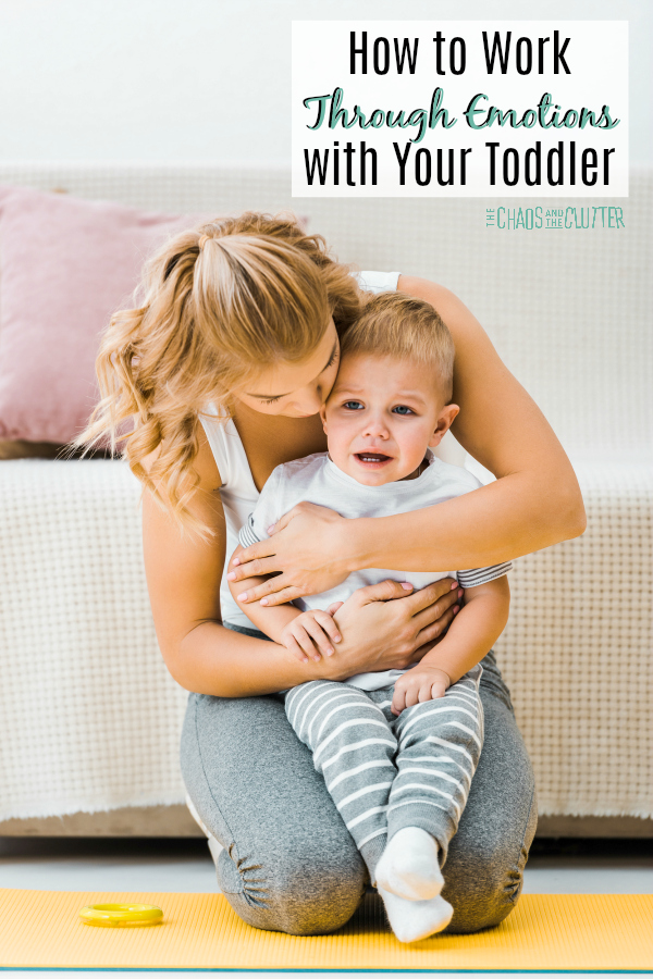 "there is a white couch with a pink pillow in the background. A blonde mom kneels in front holding her young son on her lap with her arms around him. The text reads ""How to Work Through Emotions with Your Toddler"""