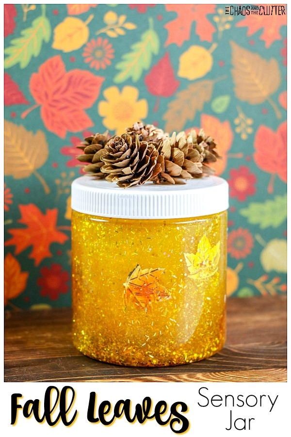 "a jar is filled with a glittery yellow mixture with foil leaves visible in it. The lid is white with pine cones on top with a background of leaves in multiple colours with text that reads ""Fall Leaves Sensory Jar"""