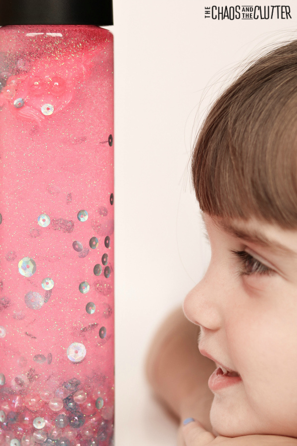 little brown haired girl looking at a bottle filled with pink liquid with sequins and glitter.