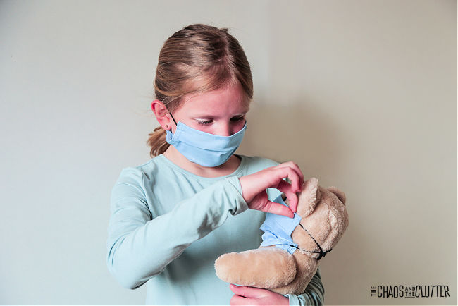 child wearing a blue face mask putting a matching mask on a teddy bear