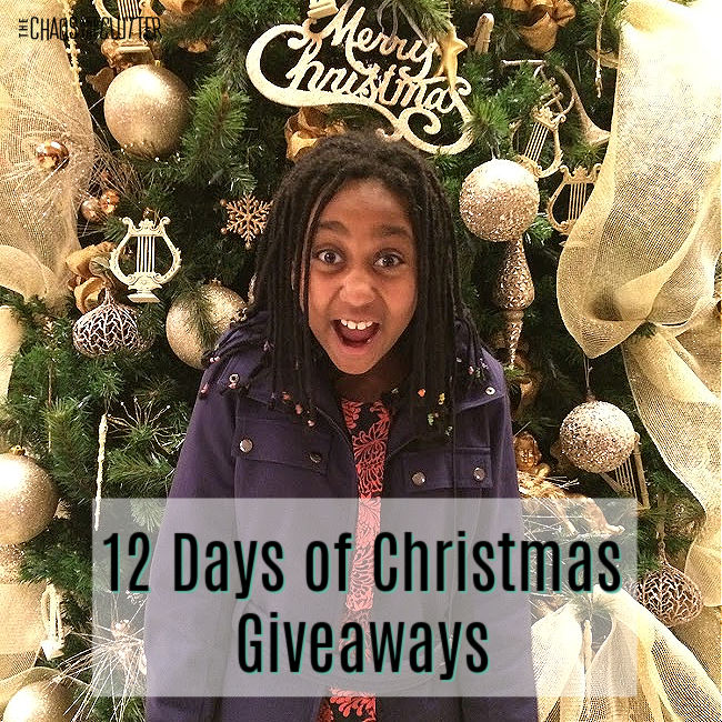 "excited girl in purple coat stands in front of a decorated Christmas tree. Text ""12 Days of Christmas Giveaways"""