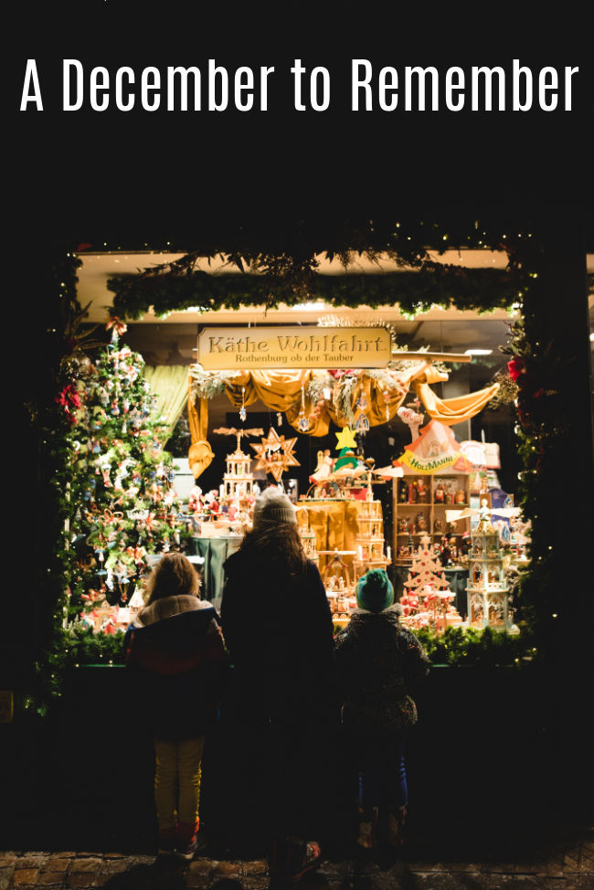 "three people looking in a window at a Christmas display. Text reads ""A December to Remember"""