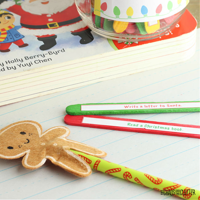gingerbread decorative topper on a holiday pencil with two popsicle sticks nearby