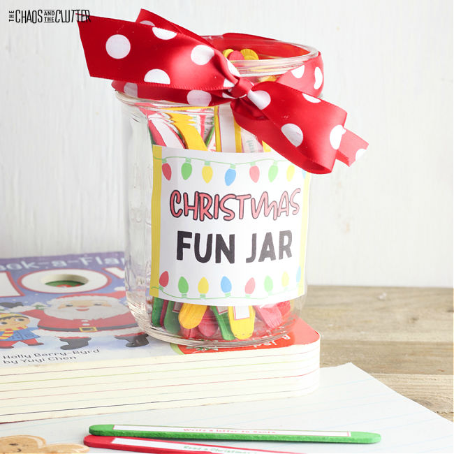 "clear jar with red and white polka dot ribbon on the top and the words ""Christmas Fun Jar"" on the side"