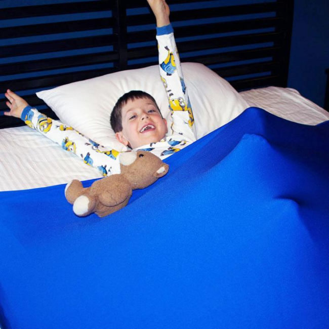 boy in bed under a stretchy blue sheet with a teddy bear