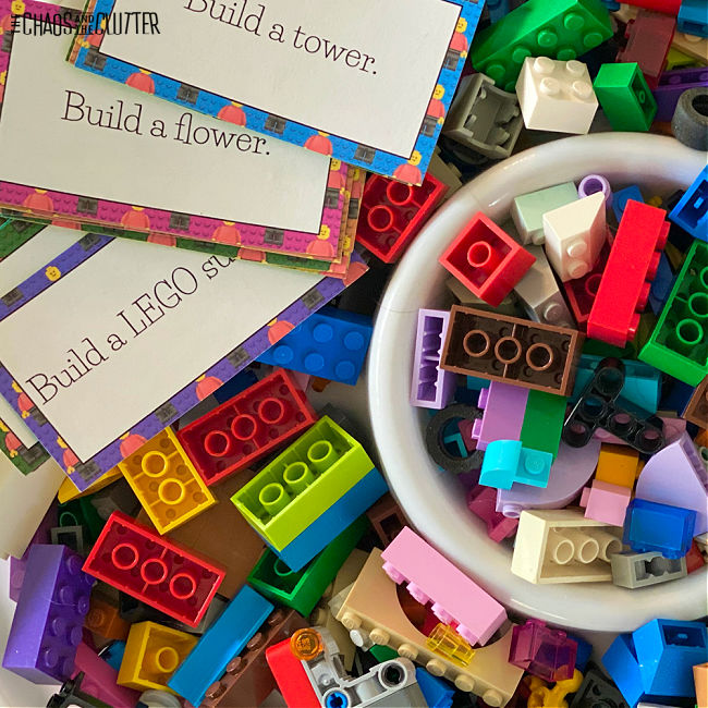 a pile of building blocks with some in a small bowl and printed instruction cards