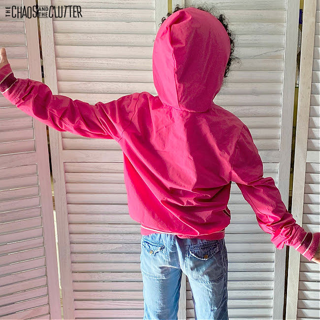girl in pink hoodie and jeans facing away from the camera