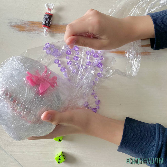 hands unwrapping a ball made of plastic wrap that has small prizes in it