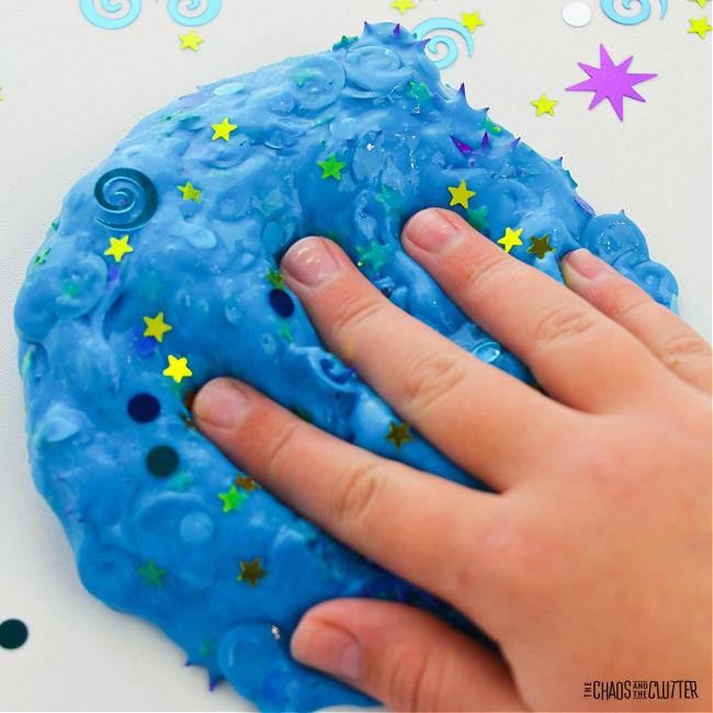 hand presses into blue slime with coloured confetti in it