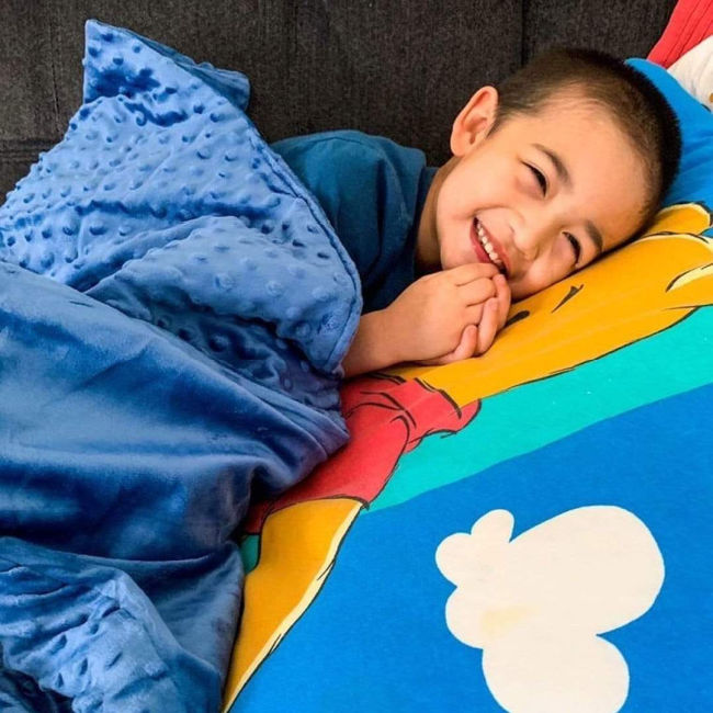 smiling boy in bed on colourful sheets under a blue blanket