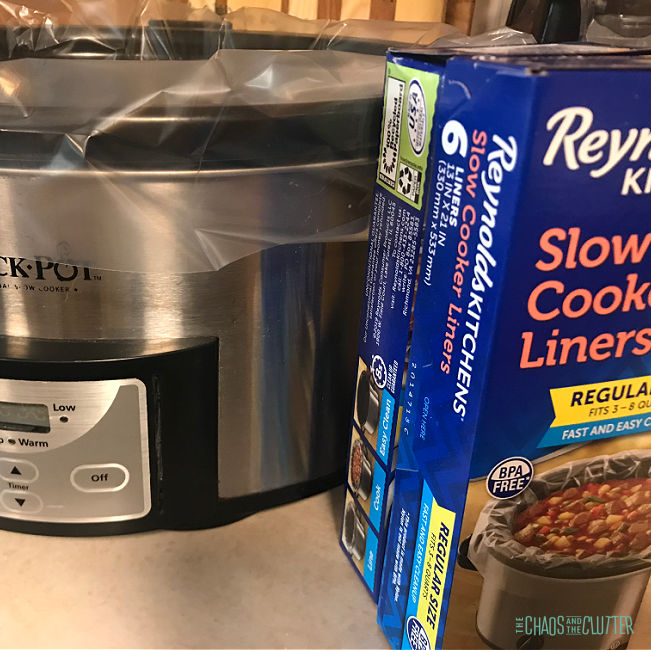 crock pot with plastic liner on counter with blue box of slow cooker liners next to it