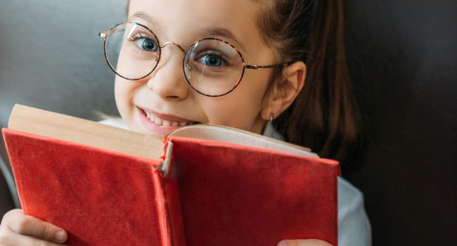 a young girl with glasses sits holding a red book