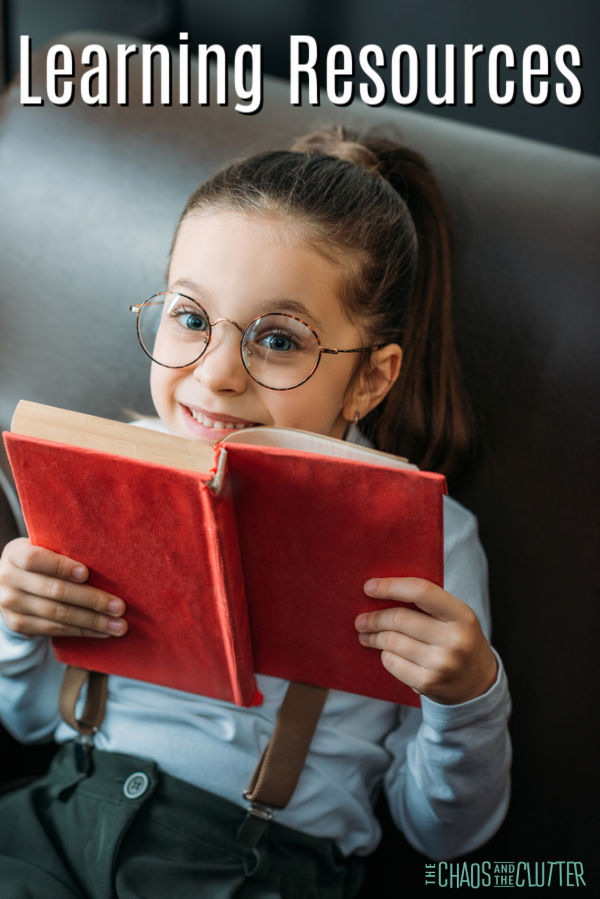little girl with glasses sitting reading a book with a red cover