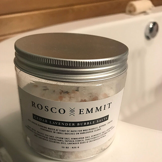 jar of bath salts sits on edge of white bathtub