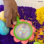 child's hand holding a magnifying glass over a sequined egg