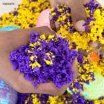 hand squishes purple and yellow Pluffle