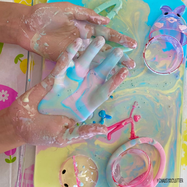 two hands covered in multiple pastel colours of goo