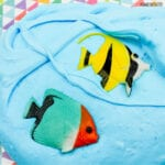 blue slime with a yellow toy fish and a green and red toy fish in it