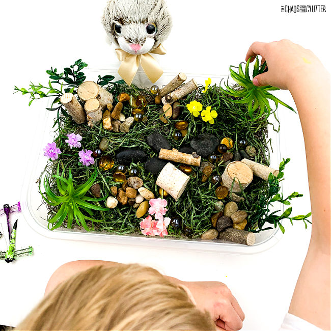 hand playing in an Easter sensory bin