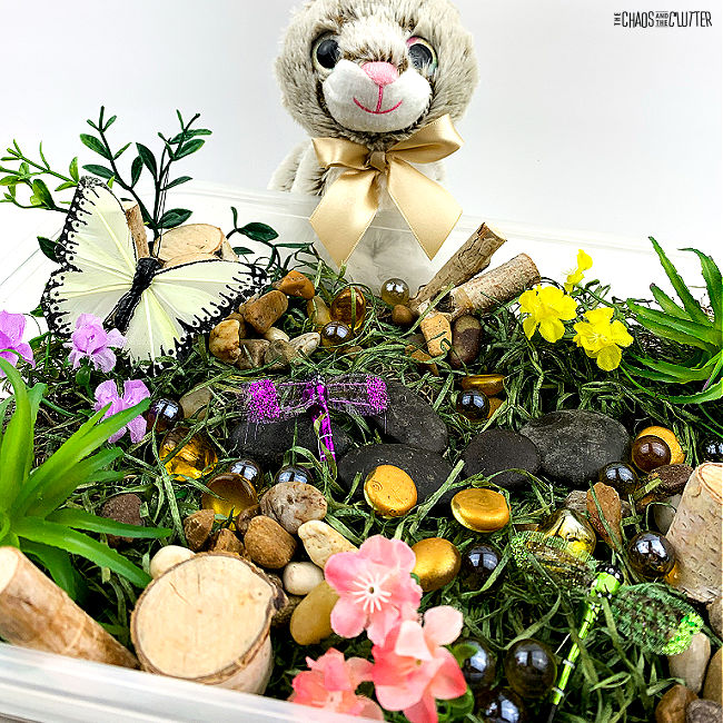 plush bunny sits by a sensory bin filled with moss, grass, and toy butterflies