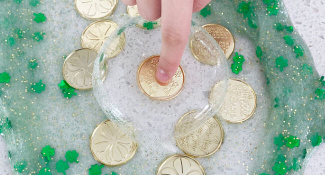finger presses into an air bubble in shamrock slime to get at a gold coin