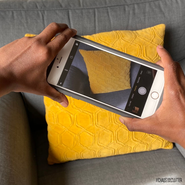 photo of a phone in a child's hands taking a photo of a yellow pillow